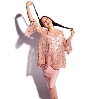 Retrato del modelo caucásico sonriente de la mujer morena hermosa en la ropa elegante del verano rosado brillante aislada en el fondo blanco.