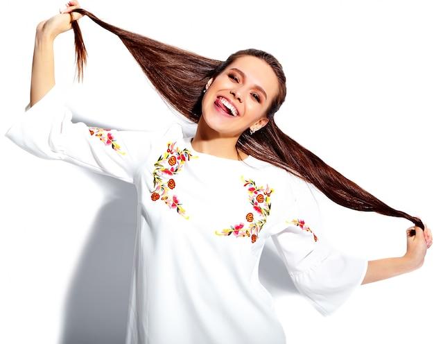 Retrato del modelo caucásico sonriente de la mujer morena hermosa en el vestido elegante del verano blanco aislado en el fondo blanco. retorciéndose el pelo
