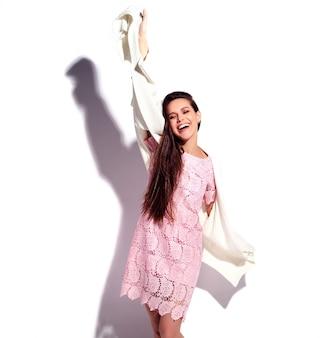 Retrato del modelo caucásico sonriente de la mujer morena hermosa en el vestido elegante del verano rosado brillante aislado en el fondo blanco. celebrando