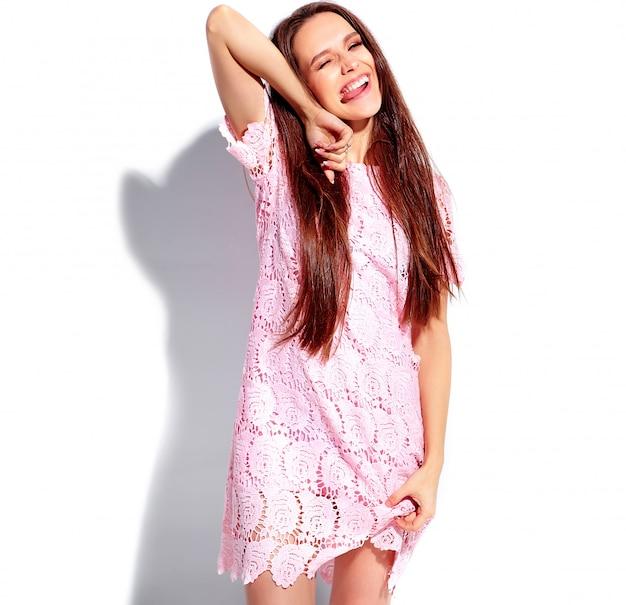Retrato del modelo caucásico sonriente de la mujer morena hermosa en el vestido elegante del verano rosado brillante aislado en el fondo blanco. haciendo un guiño y mostrando su lengua