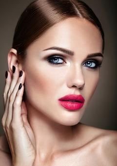 Retrato de modelo de chica hermosa con maquillaje de noche y peinado romántico tocando su piel. labios rosados