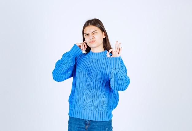 Retrato de un modelo de chica joven coning su oreja y mostrando un gesto ok.