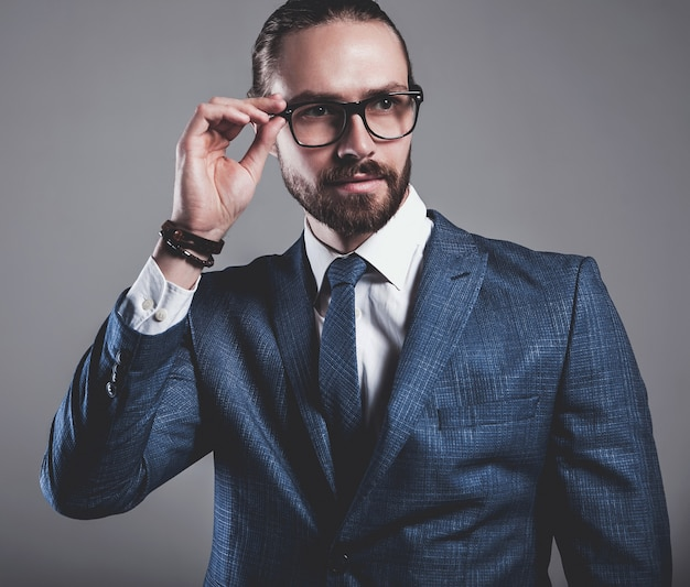Retrato del modelo de empresario de moda guapo vestido con elegante traje azul con gafas