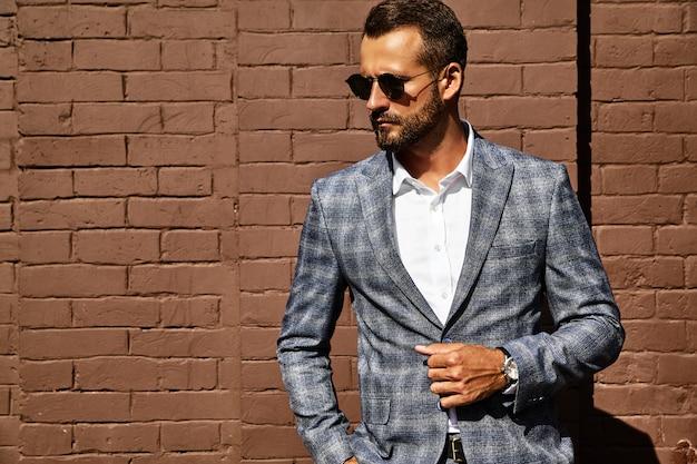 Retrato del modelo de empresario de moda guapo vestido con elegante traje a cuadros posando en la calle