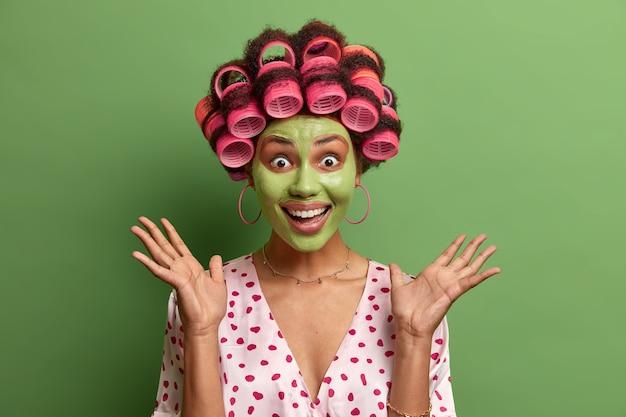Retrato de modelo femenino muy contento levanta las palmas y hace procedimientos matutinos, aplica mascarilla facial verde hidratante para rejuvenecer, usa rulos, aislado en verde, vestido informal