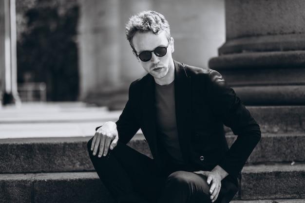 Retrato modelo del hombre joven que se sienta en las escaleras