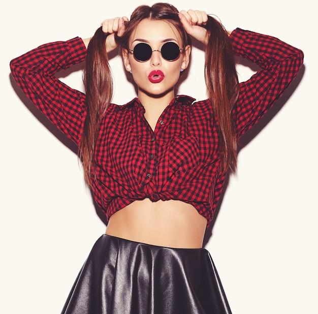 Retrato del modelo joven feliz de la mujer con maquillaje brillante y labios coloridos en camisa a cuadros roja del verano y gafas de sol aisladas en blanco. volviéndose loco