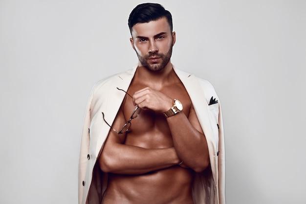 Retrato de modelo masculino de ajuste elegante en un traje ligero con gafas aislado en la pared blanca