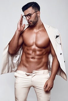 Retrato de modelo masculino elegante en un traje ligero aislado en la pared blanca