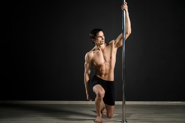 Retrato de modelo masculino realizando un pole dance