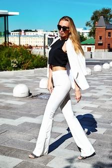 Retrato del modelo moderno de la empresaria de la moda atractiva en el traje blanco que presenta en el fondo de la calle detrás del cielo azul. caminando