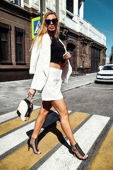 Retrato del modelo moderno de la empresaria de la moda atractiva en el traje blanco que presenta en el fondo de la calle detrás del cielo azul. paso de cebra