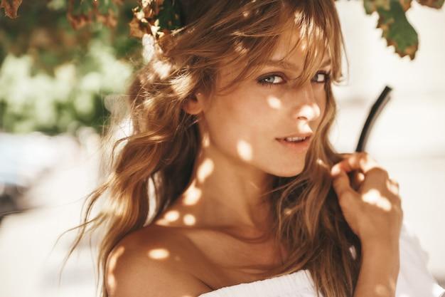 El retrato del modelo rubio lindo hermoso del adolescente sin maquillaje en ropa blanca del vestido del inconformista del verano que presenta en el fondo de la calle. luces de sol en la cara