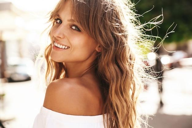 Retrato del modelo rubio sonriente lindo hermoso del adolescente sin maquillaje en el vestido blanco del inconformista del verano que presenta en el fondo de la calle. giro de vuelta