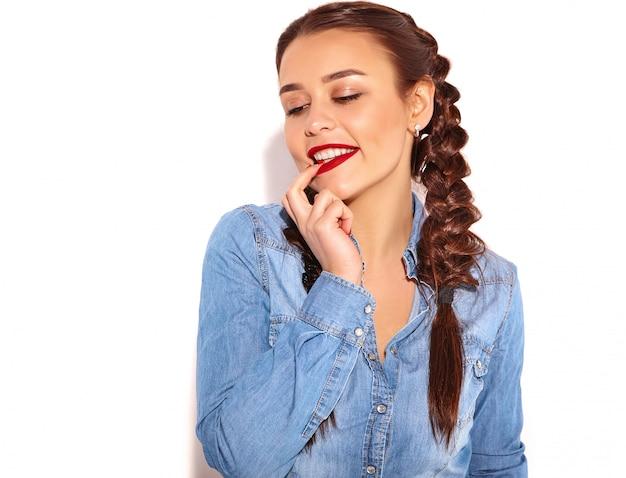 Retrato del modelo sonriente feliz joven de la mujer con maquillaje brillante y labios rojos con dos coletas en la ropa de los tejanos del verano aislada.