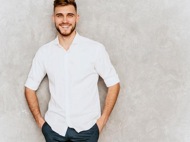 Retrato del modelo sonriente hermoso del hombre de negocios del inconformista que lleva la camisa blanca casual del verano.