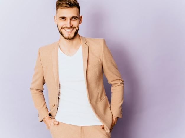 Retrato del modelo sonriente hermoso del hombre de negocios del inconformista que lleva el traje beige casual.