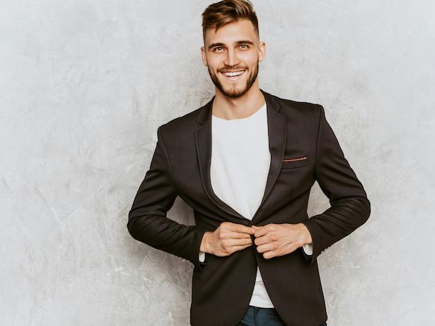 Retrato del modelo sonriente hermoso del hombre de negocios del inconformista que lleva el traje negro casual.