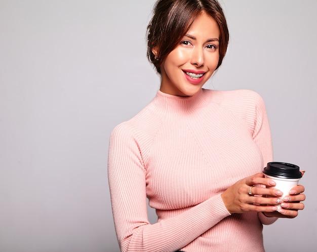 Retrato del modelo sonriente lindo hermoso de la mujer morena en ropa casual del rosa del verano sin maquillaje aislado en gris.