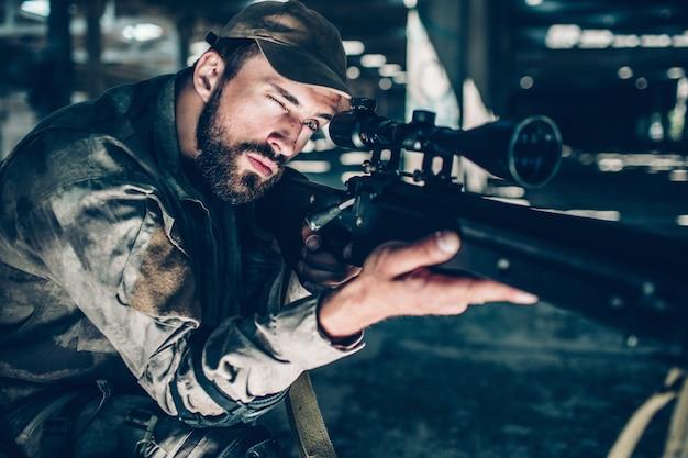 Retrato de morena está apuntando. él está mirando a través de la lente. guy sostiene el rifle con la mano derecha y mantiene el izquierdo en el gatillo. el hombre está listo para disparar.