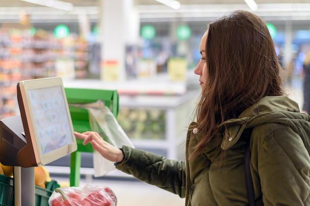 Retrato de morena en supermercado pesando verduras en balanzas electrónicas con pantalla táctil