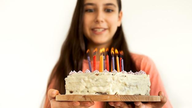 Retrato de muchacha adolescente latina alegre que sopla una vela en la torta de cumpleaños. agitando la fiesta de cumpleaños feliz en casa. fondo de pared blanca.