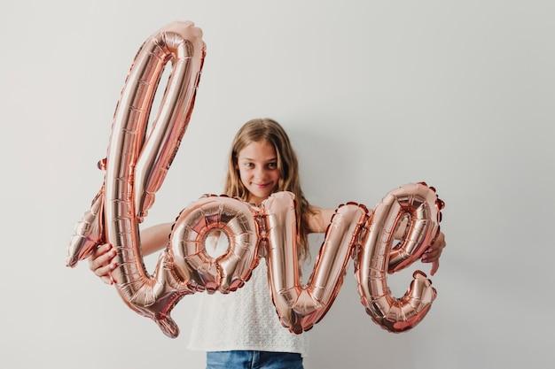 El retrato de una muchacha adolescente linda alegre que sostiene un globo rosado con amor forma en casa. concepto de felicidad y estilo de vida.