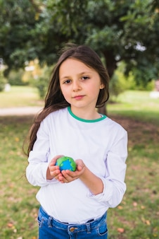 Retrato de una muchacha adorable que sostiene el mundo del planeta de la arcilla en parque