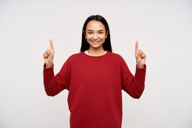 Retrato de muchacha asiática atractiva, adulta con el pelo largo oscuro. vistiendo un suéter rojo y apuntando hacia el espacio de la copia. sonrisa segura. mirando a la cámara aislada sobre fondo blanco.