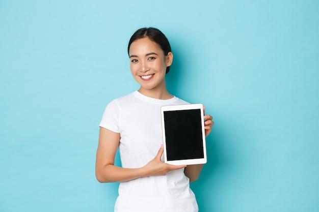 El retrato de la muchacha asiática atractiva sonriente demuestra el proyecto o el anuncio en la pantalla de la tableta digital, presenta el nuevo sitio de compras, de pie optimista sobre el fondo azul claro.