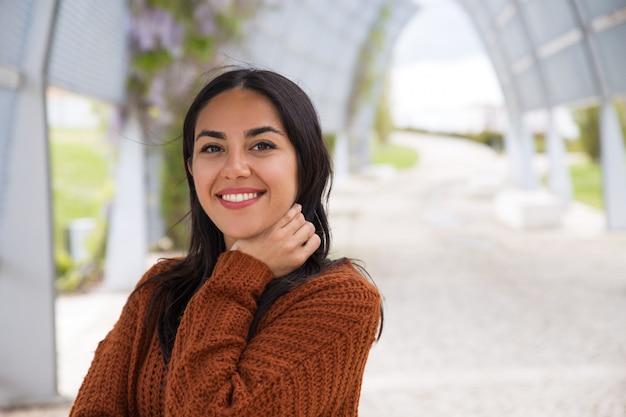 Retrato de la muchacha asiática emocionada feliz que ajusta el pelo