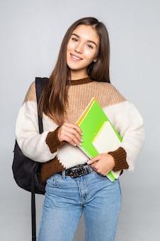 Retrato de muchacha atractiva linda joven estudiante aislada en la pared blanca