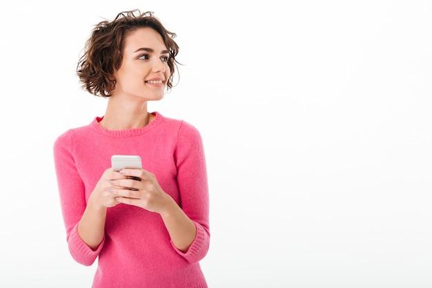 Retrato de una muchacha atractiva sonriente que sostiene el teléfono móvil