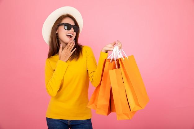 El retrato de una muchacha bonita asiática feliz que lleva a cabo compras naranja empaqueta lejos