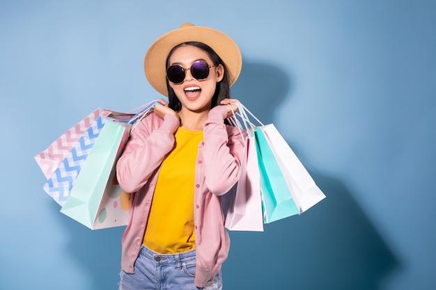 Retrato de una muchacha bonita asiática feliz que sostiene bolsos de compras lejos