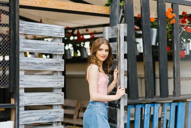 Retrato de una muchacha bonita y hermosa de pie en una puerta de madera. el concepto de una nueva vida o la finalización de la anterior.