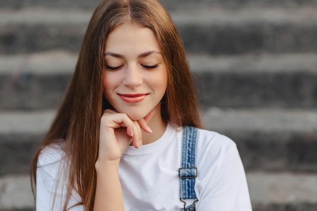 Retrato de la muchacha bonita joven que se sienta en las escaleras