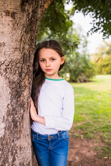 Retrato de una muchacha bonita que se coloca cerca de tronco de árbol en parque