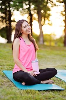 Retrato de una muchacha bonita en ropa deportiva de color rosa, que sostiene una botella de agua o un cóctel de proteínas.