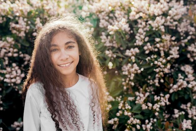 Retrato de una muchacha bonita sonriente en luz del sol