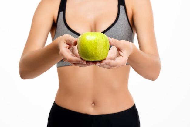 Retrato de la muchacha deportiva hermosa joven que sostiene la manzana sobre el fondo blanco.