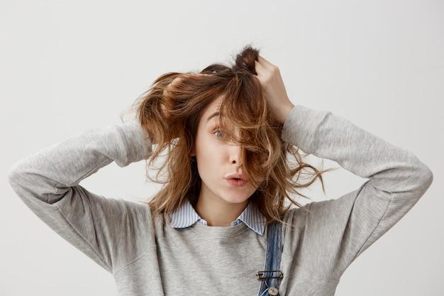 Retrato de la muchacha divertida que toca su pelo castaño hermoso mientras que pasa el día libre en casa estando solo. mujer morena en casual posando con agradables expresiones faciales. de cerca