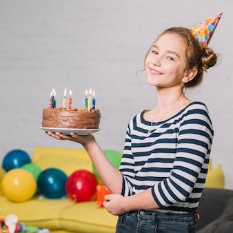 Retrato de una muchacha feliz que sostiene la torta deliciosa en la placa blanca en el partido