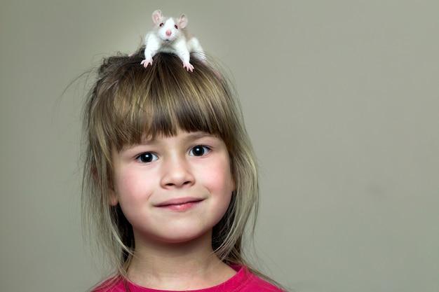 Retrato de la muchacha feliz sonriente linda del niño lindo con el hámster blanco del ratón del animal doméstico en la cabeza en la pared ligera. mantener a las mascotas en casa, cuidar y amar al concepto de animales.
