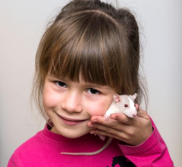 Retrato de la muchacha feliz sonriente del niño lindo con el hámster blanco del ratón del animal doméstico en fondo del espacio de la copia ligera. mantener a las mascotas en casa, cuidar y amar al concepto de animales.