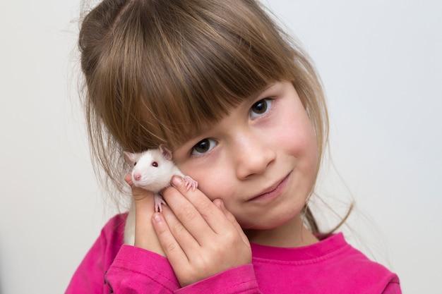Retrato de la muchacha feliz sonriente del niño lindo con el hámster blanco del ratón del animal doméstico en luz. mantener mascotas en casa, cuidar y amar a los animales.