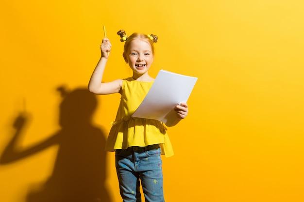 Retrato de una muchacha hermosa en una blusa amarilla y tejanos.