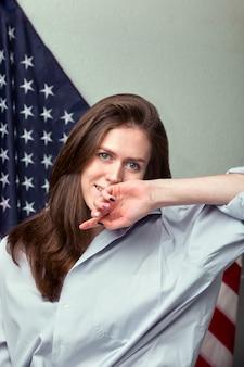 Retrato de muchacha hermosa en camisa sobre fondo de bandera americana de cerca