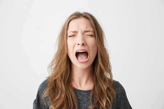 Retrato de muchacha hermosa joven emotiva gritando con los ojos cerrados.