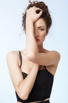 Retrato de muchacha hermosa con maquillaje brillante. pared azul